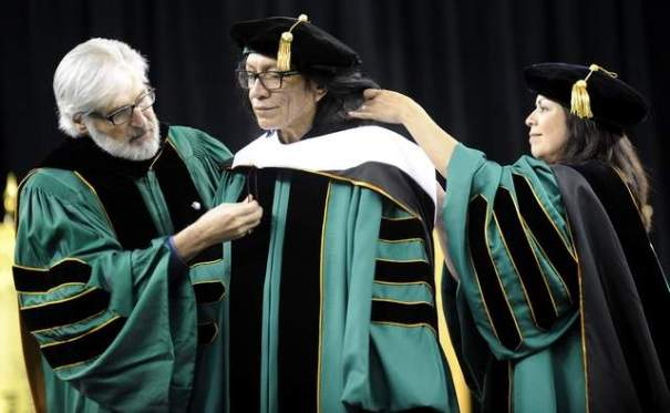 Paul Massaron and Sandra Hughes O'Brien, members of the Wayne State University Board of Governors, put the sash on Sixto Rodriguez during commencement ceremonies at Ford Field. (David Coates/The Detroit News)